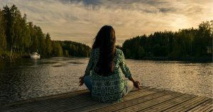 a mature woman meditating by a lake: an example of home remedies for fibromyalgia