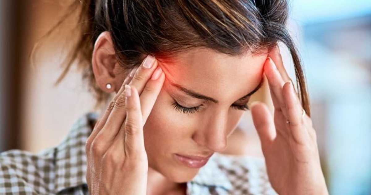a woman rubbing her temples, experiencing chronic pain from headaches