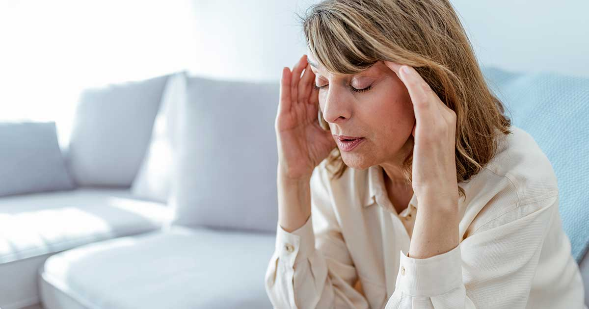 a woman holding her head feeling pain and fatigue, which is one way fibromyalgia starts