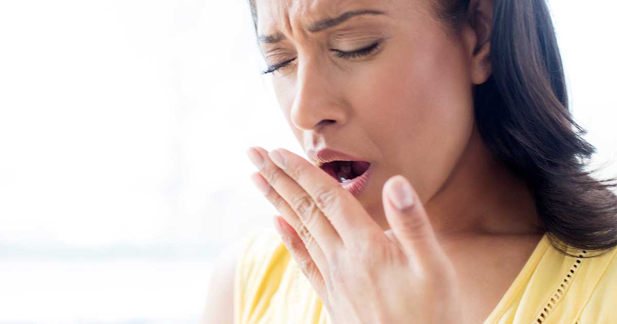A woman wearing a yellow shirt to cover her mouth to yawn.